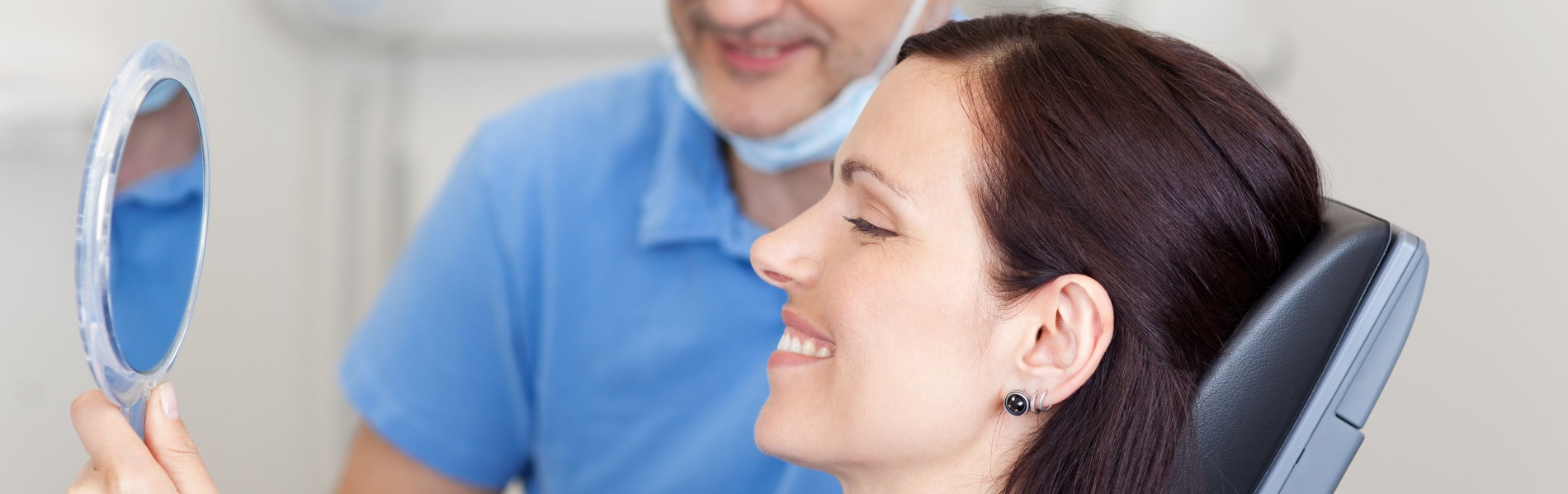 An image of a smiling woman looking in a mirror portrays the concept of restorative dentistry at Discovery Smiles Dentistry.